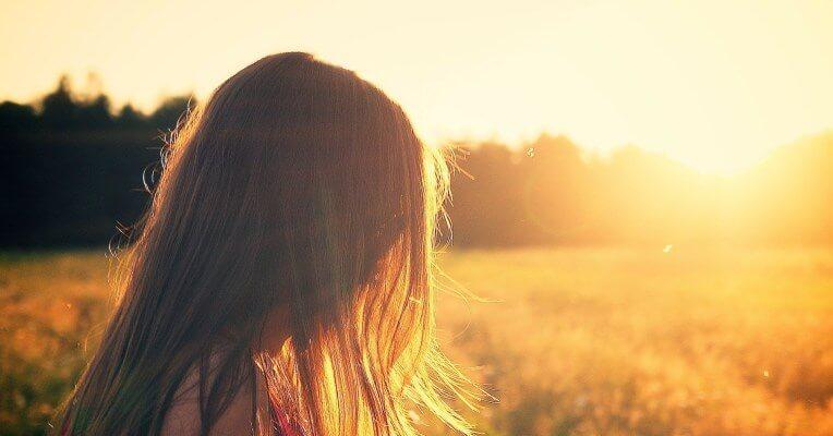 Girl in field with sun shining